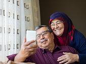 Senior couple using mobile phone, home interior