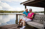 Happy senior couple using mobile phone to deposit bank check on wooden bench near pond