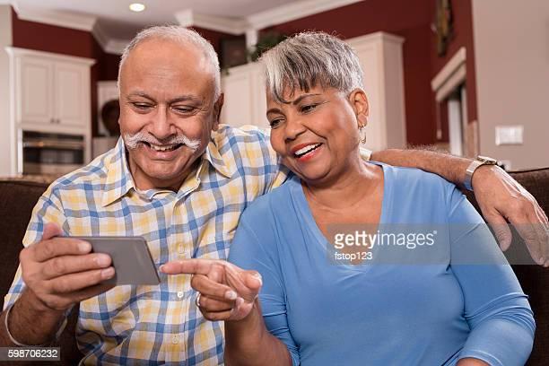 Senior couple using smart phone at home.