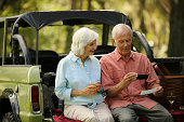 Happy senior couple using smart phone to deposit check while sitting in back of SUV car