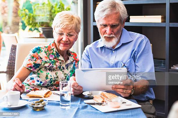 Senior Couple using tablet during breakfast in the cafe