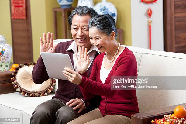 Senior couple video chatting with digital tablet in Chinese New Year