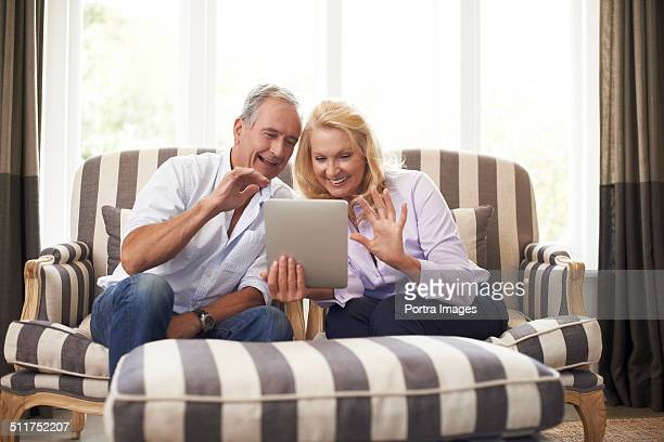 Senior couple video conferencing on digital tablet