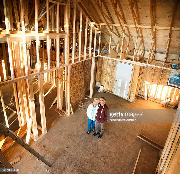 Senior couple visiting construction site of new home