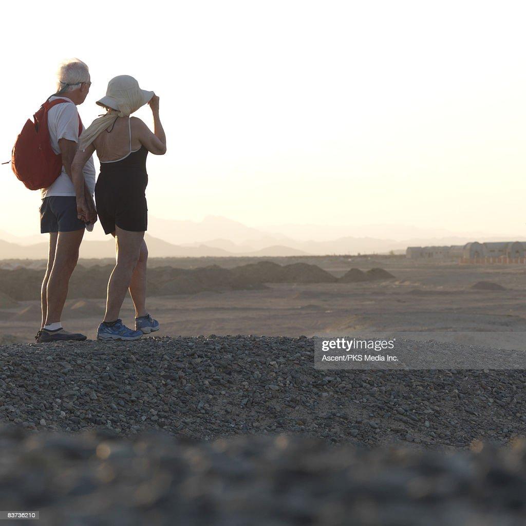 Senior couple walk through desert landscape : Stock Photo