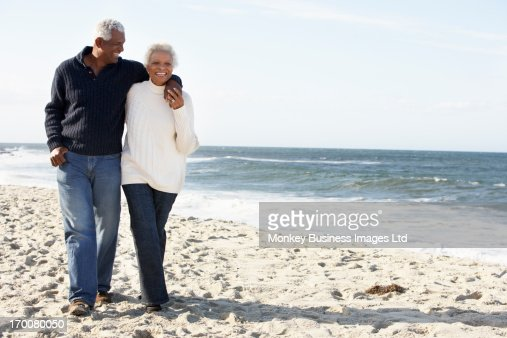 Senior Couple Walking Along Beach Together : Stock Photo