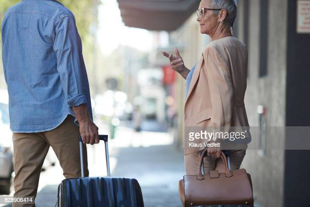 Senior couple walking and talking with rolling suitcases on city street