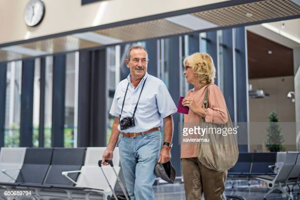 Senior couple walking at departure area in airport