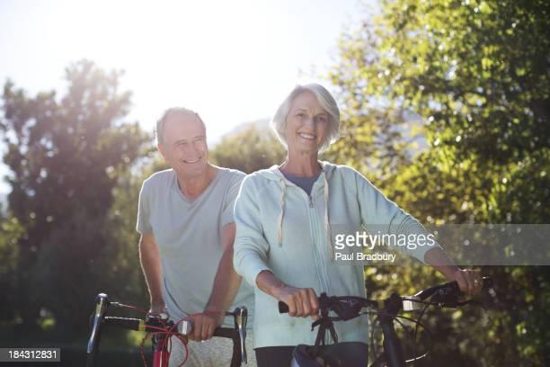 Altes Paar walking im park Fahrräder