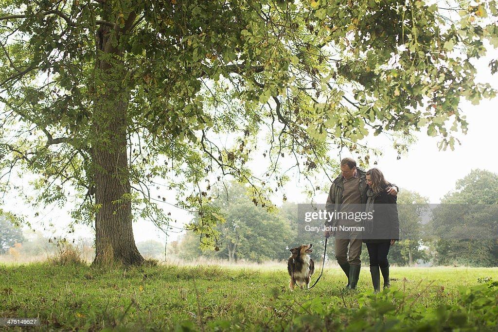 Senior couple walking dog, Norfolk, UK