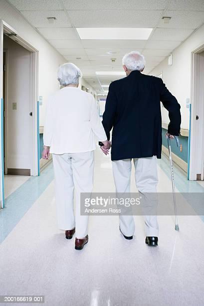 Senior couple walking down hospital corridor, holding hands, rear view