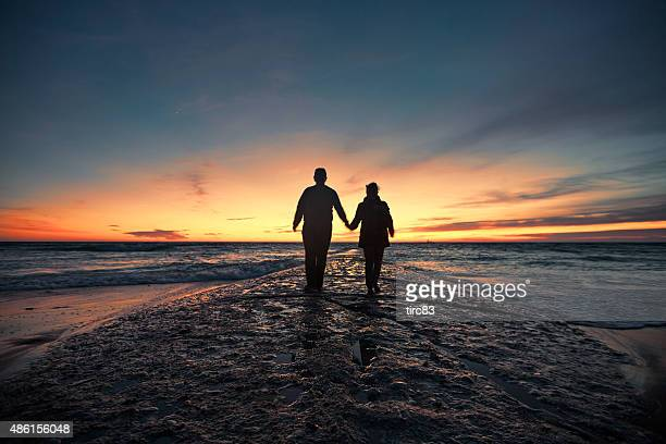 Senior couple marche du bord de mer au coucher du soleil