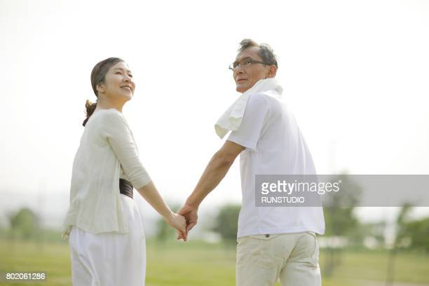 Senior couple walking hand in hand in the park