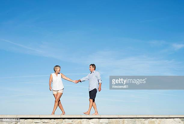 Senior couple walking hand in hand on a wall in front of sky