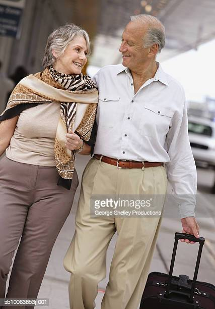 Senior couple walking in airport area