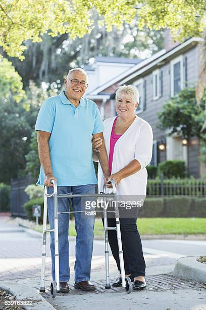 Senior couple walking in neighborhood, man with walker
