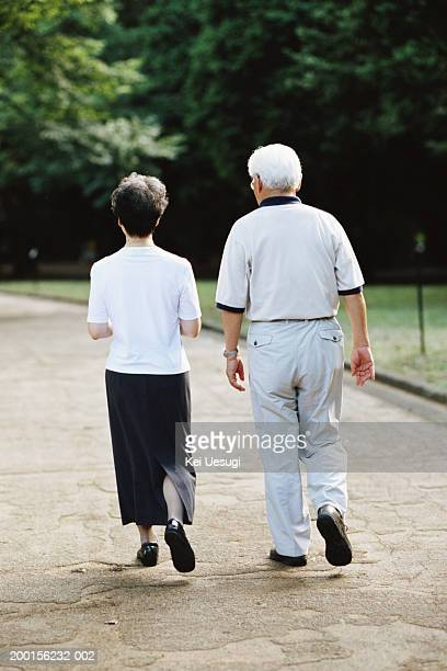 Senior couple walking in park, rear view