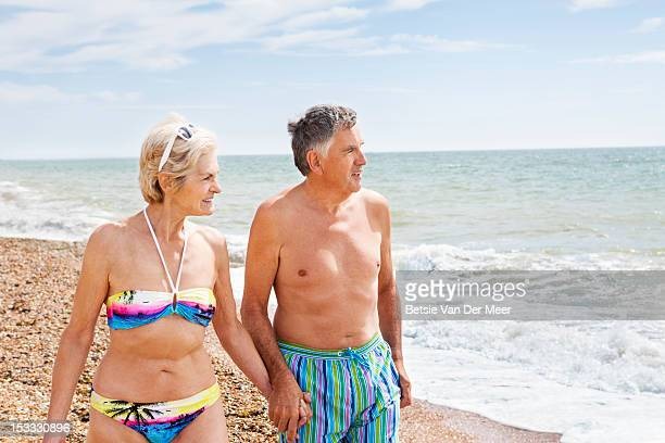 Senior couple walking on beach.