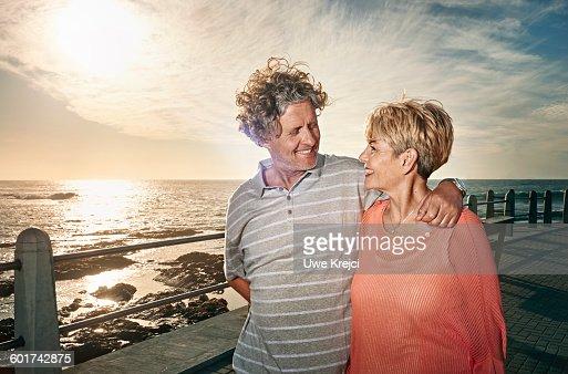 Senior couple walking on pier at sunset