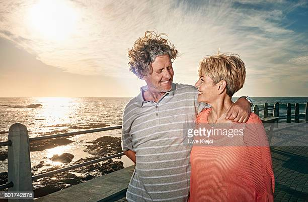 Senior couple walking on pier at sunset