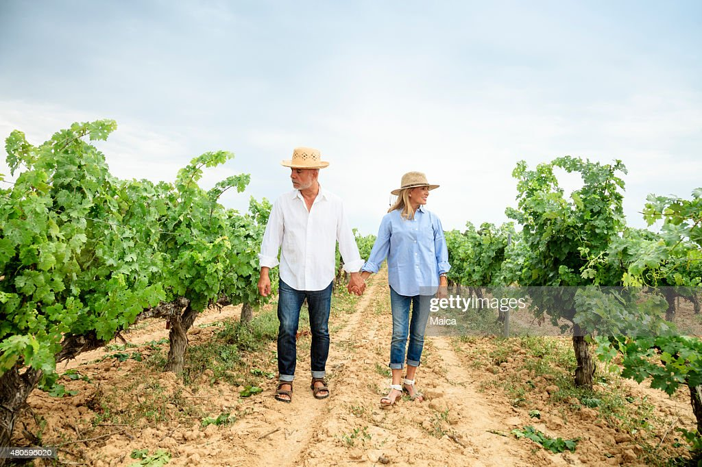 Senior couple walking through vineyards. : Stock Photo