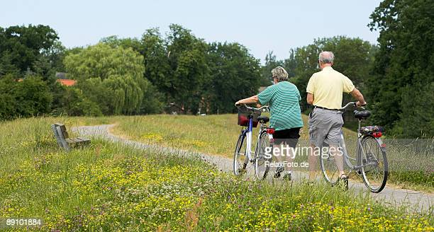 Senior couple walking with bicycles in summer on dyke