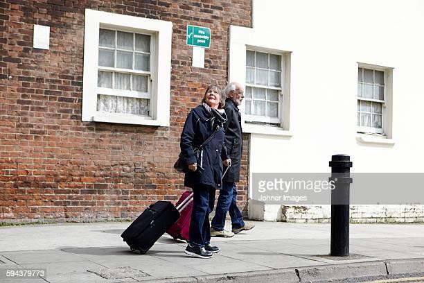 Senior couple walking with luggage