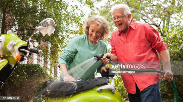 Senior couple washing motor scooter.