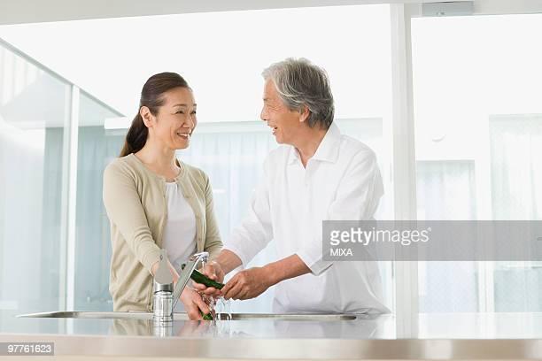 Senior couple washing vegetables