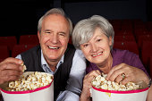 Senior Couple Watching Film In Cinema