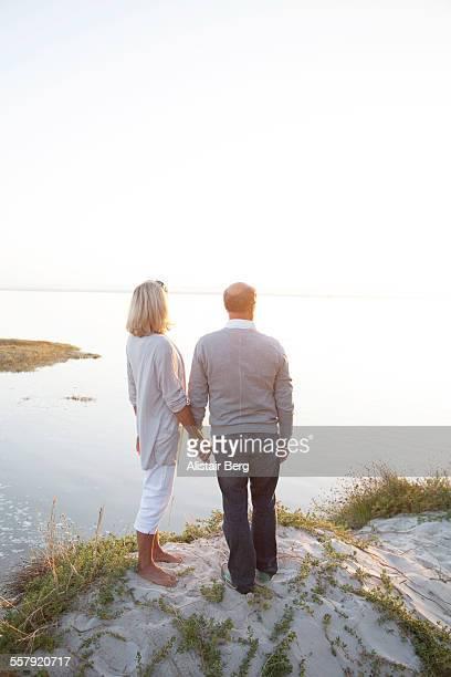 Senior couple watching sunset on beach