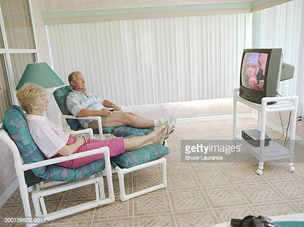 Senior couple watching television in den, side view