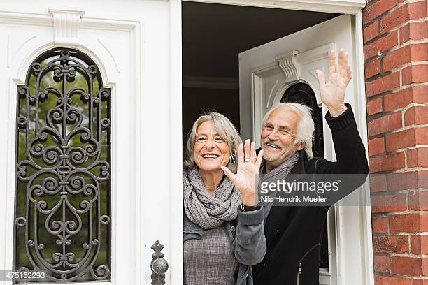 Senior couple waving by front door
