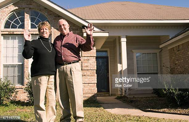 Senior Couple waving in front of house