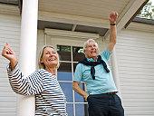 Senior couple waving on veranda