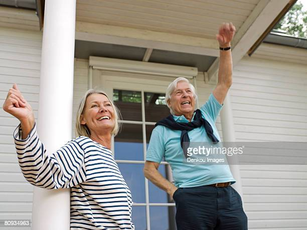 Senior couple waving on veranda