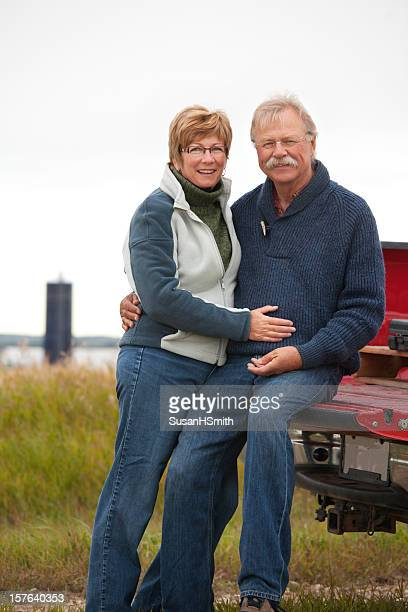 Senior couple wearing jeans sitting on red truck bed