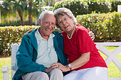 Senior couple with arm around sitting on a park bench