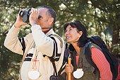 Senior couple with binoculars in woods