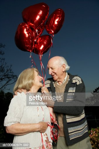 Senior couple with bunch of heart shaped balloons, looking in eyes : Stock Photo