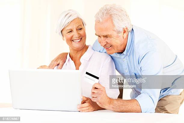 Senior Couple With Credit Card Doing Online Shopping On Laptop