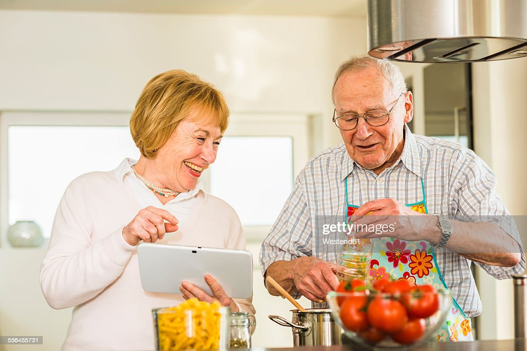 Senior couple with digital tablet cooking in kitchen
