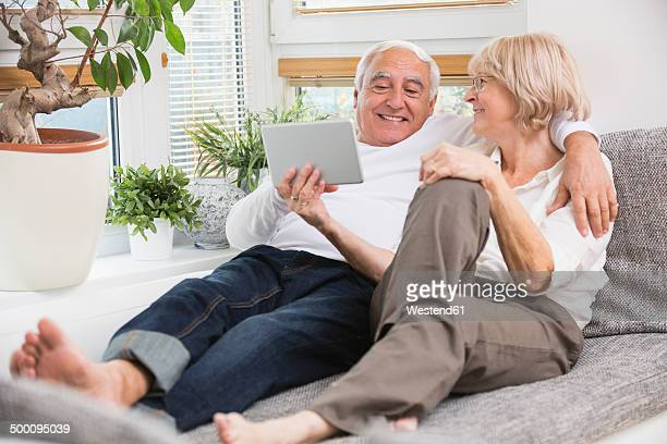 Senior couple with digital tablet side by side on sofa in living room