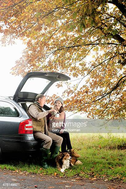 Senior couple with dogs sharing coffee from car boot, Norfolk, UK