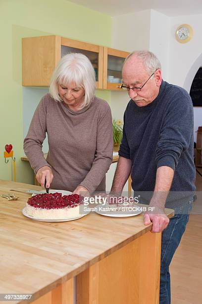 Senior couple with fruit cake in kitchen
