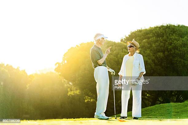 Senior couple with golf clubs walking on footpath