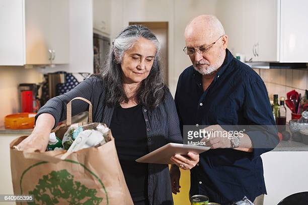 Senior couple with grocery bag using digital tablet in kitchen