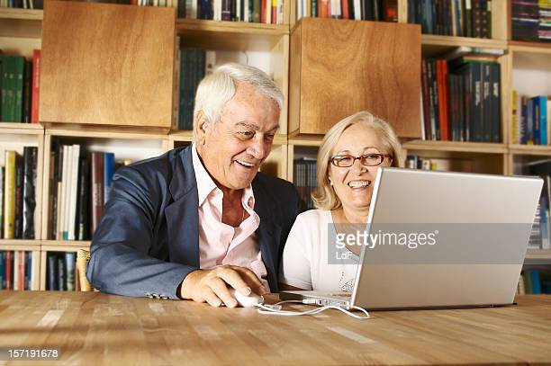 Senior couple with laptop and books shelves on the background