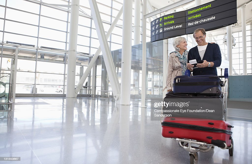 Senior couple with luggage at airport
