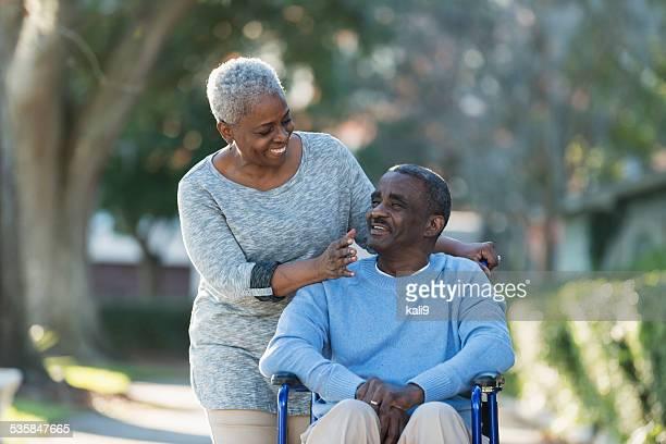 Altes Paar mit Mann im Rollstuhl